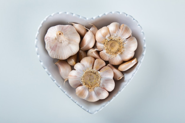 Spicchi d'aglio e lampadina nella ciotola del cuore con sfondo bianco.