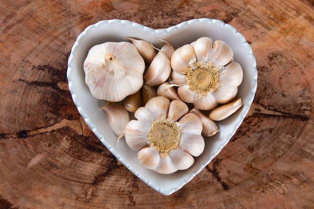 Spicchi d'aglio e lampadina nella ciotola del cuore con uno sfondo di legno.