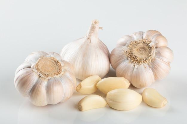 Spicchi d'aglio e bulbo isolato su sfondo bianco..