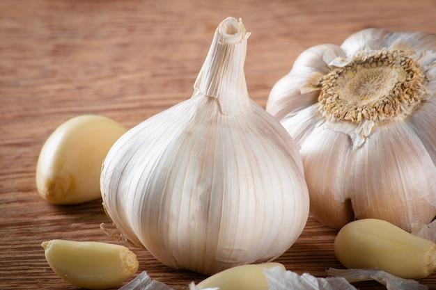 Spicchi d'aglio e bulbo isolato su sfondo di legno..