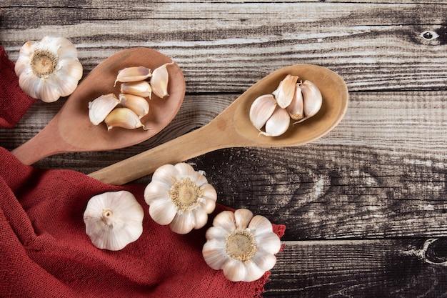 Spicchi d'aglio e lampadina sulla tavola di legno e tessuto rosso.