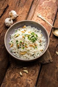 Riso fritto all'aglio o pulav con riso basmati e lahsun, servito con dal tadka su sfondo lunatico, messa a fuoco selettiva