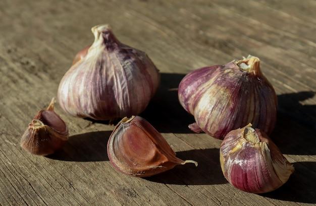 L'aglio coltivato dagli agricoltori giace su una tavola di legno e si asciuga il concetto di coltivazione di ortaggi