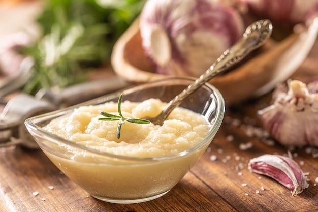 Pasta d'aglio in una ciotola di vetro con aglio sbucciato, sale, frantoio e teste d'aglio.