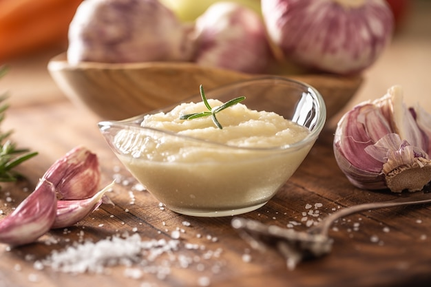 Pasta d'aglio in una ciotola di vetro con aglio sbucciato, sale e teste d'aglio.