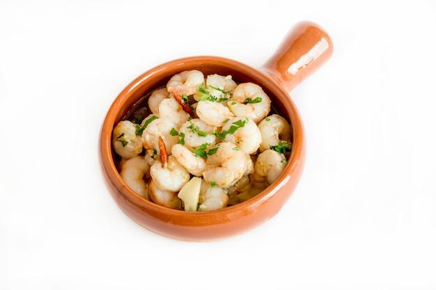 Gamberetti all'aglio serviti in una pentola di terracotta