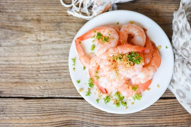 Gamberetti all'aglio sbucciati su fondo bianco tavolo da pranzo cibo, gamberi freschi frutti di mare