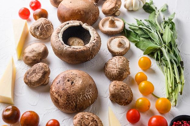Funghi all'aglio ingredienti per cuocere portobello, formaggio cheddar, pomodorini e salvia su sfondo bianco, vista laterale del fuoco selettivo.