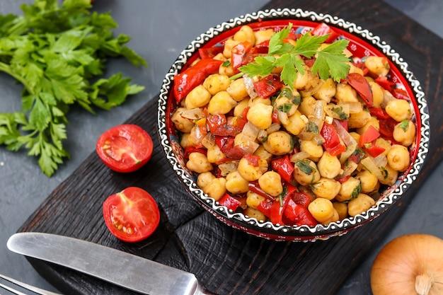 Guarnire di ceci con pepe e pomodori, un piatto vegetariano ricco di proteine, che si trova in un piatto su una superficie scura orizzontalmente, primo piano, vista dall'alto