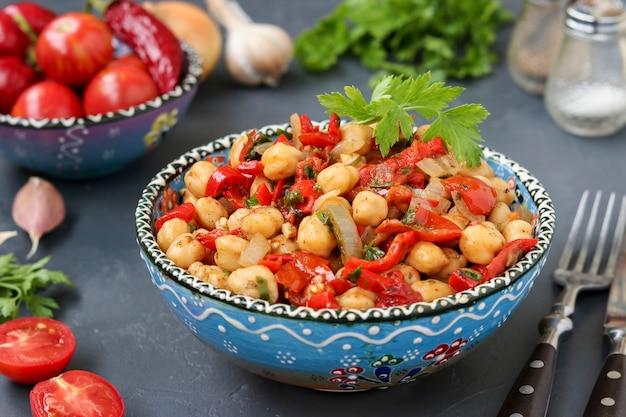 Guarnire di ceci con pepe e pomodori, un piatto vegetariano ricco di proteine, situato in un piatto contro una superficie scura in orizzontale, primo piano