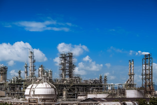 Torre di distillazione del gas e fumaiolo di impianti industriali petroliferi su sfondo blu cielo, a valle della centrale petrolifera fossile