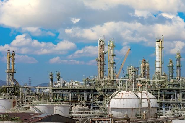 Torre di distillazione del gas e pila di fumo dell'impianto industriale del petrolio sullo sfondo del cielo blu