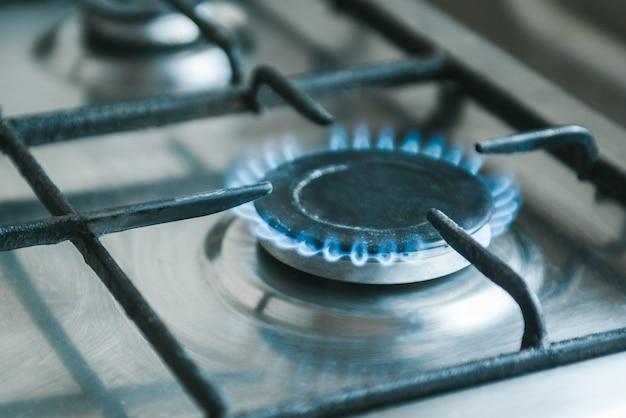 Gas. stufa della cucina con fiamme blu che bruciano.