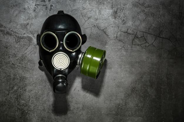 Maschera antigas su uno sfondo di pietra nera con una cartuccia filtrante verde. concetto post-apocalittico.