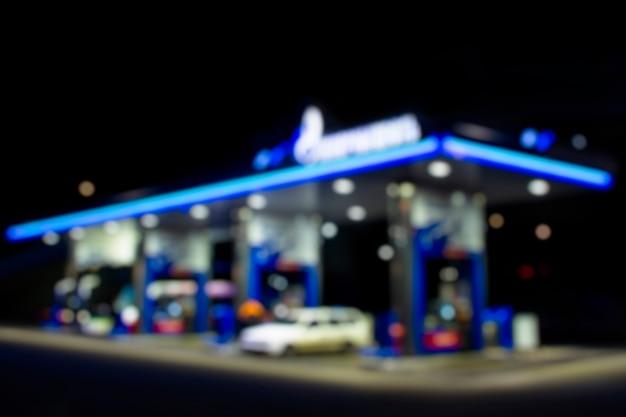 Distributore di benzina di notte. l'auto è alimentata a benzina. foto sfocata per lo sfondo.