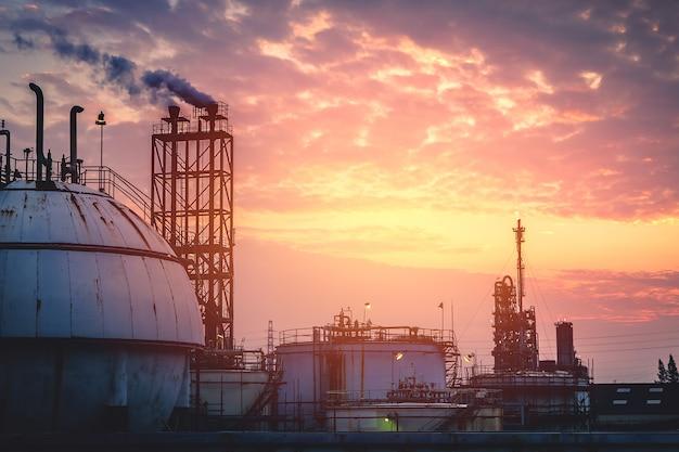 Carro armato della sfera di stoccaggio del gas con il fumaiolo sul cielo di tramonto