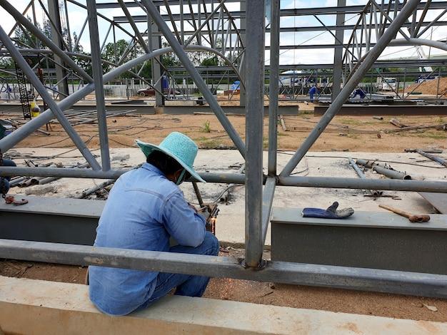 Saldatura a gas e taglio della struttura in acciaio da parte di un tecnico di saldatura presso edificio industriale di costruzione