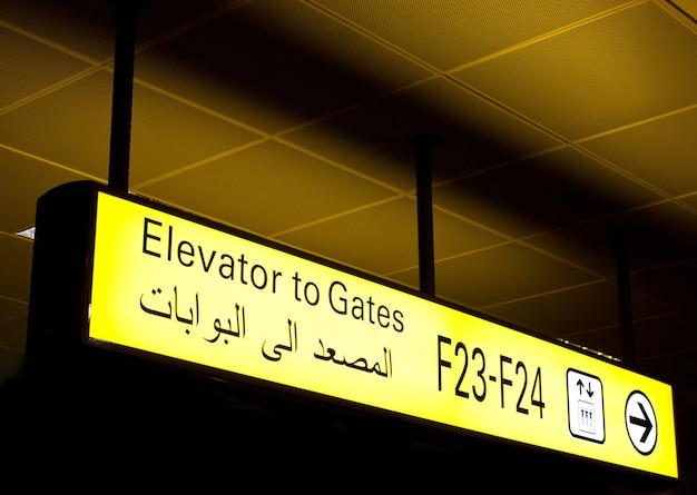 Segno di porta in un aeroporto internazionale in medio oriente con informazioni arabe