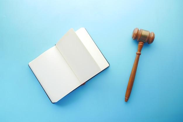 Martelletto e libro con copia spazio su sfondo blu