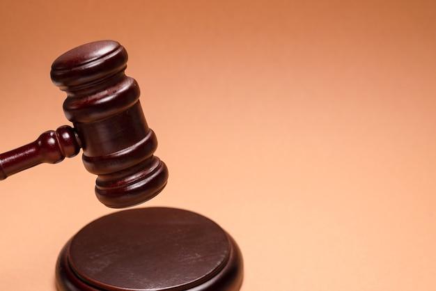 Gavel giù sul supporto su sfondo marrone. giustizia del sistema giuridico concettuale. copia spazio.