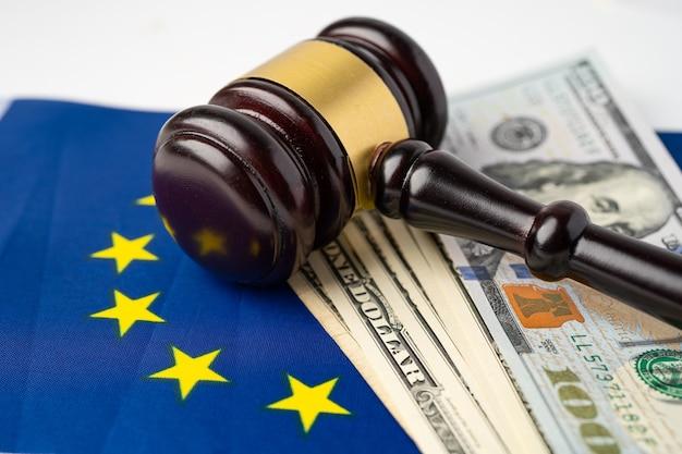 Martelletto per avvocato giudice e banconote in dollari usa sulla bandiera dell'ue. Foto Premium