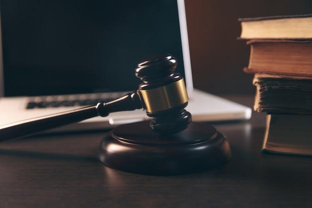 Martelletto, laptop, libri e bilance su sfondo marrone, concetto legale di tribunale giudiziario e legislativo. sfondo avvocato flatlay vista dall'alto