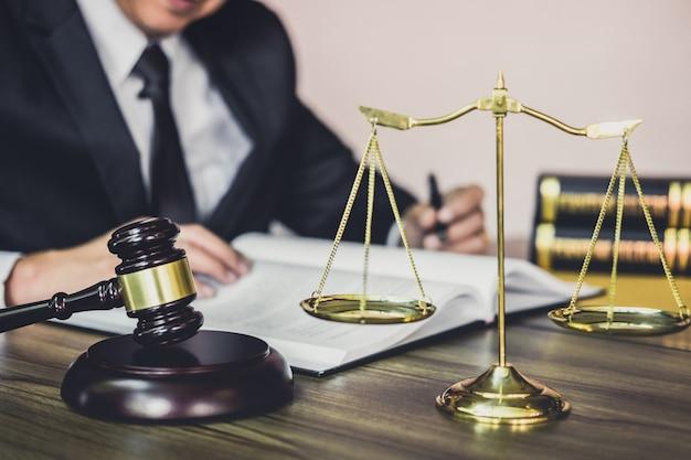 Martelletto sul tavolo in legno e avvocato avvocato o maschio che lavora su una documentazione in studio legale in ufficio