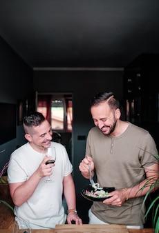 Coppia gay cenare su un'insalata e bere vino in casa
