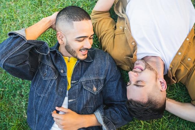 Coppie gay che indicano sull'erba al parco.