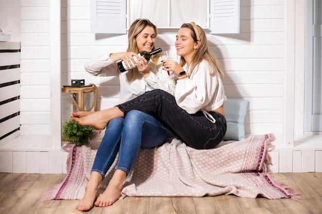 Coppia gay due belle giovani donne, festa romantica lgbt con vino rosso a casa, felicità, abbraccio, relazione familiare
