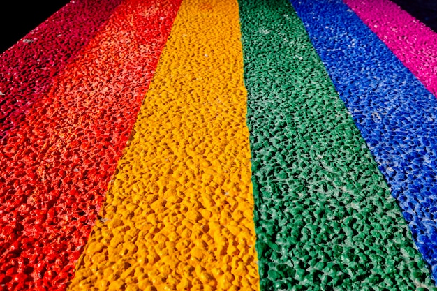 Bandiera gay dipinta sul cemento duro di una panchina di pietra.