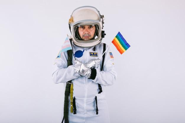 Cosmonauta gay maschio in tuta spaziale e casco, tenendo la bandiera arcobaleno lgtbi, su sfondo bianco.
