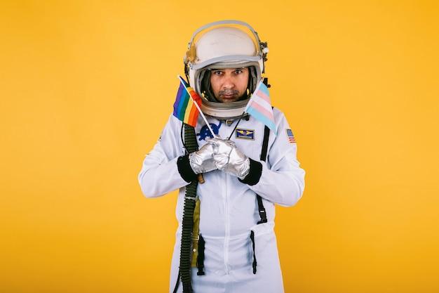 Cosmonauta maschio transessuale gay con gesto serio in tuta spaziale e casco, che tiene la bandiera arcobaleno lgtbi e la bandiera transgender, sul muro giallo.