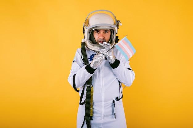Cosmonauta maschio transessuale gay con gesto serio in tuta spaziale e casco, che tiene la bandiera transgender, sulla parete gialla.