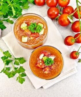 Zuppa di pomodoro gazpacho in due bicchieri con prezzemolo e verdure su un tovagliolo sullo sfondo del tavolo in pietra