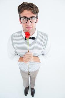 Pantaloni a vita bassa geeky che tengono una rosa rossa