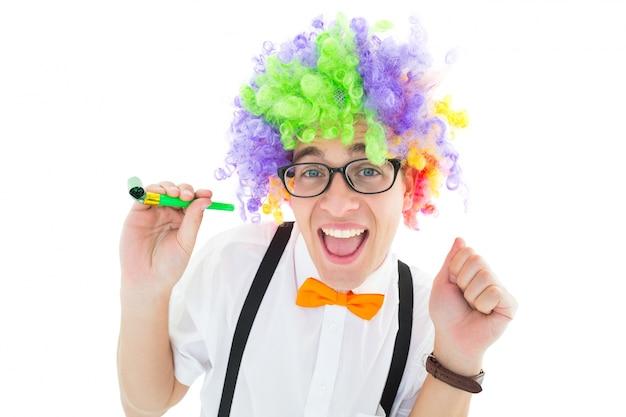 Pantaloni a vita bassa geeky che indossano una parrucca dell'arcobaleno che tiene il corno del partito