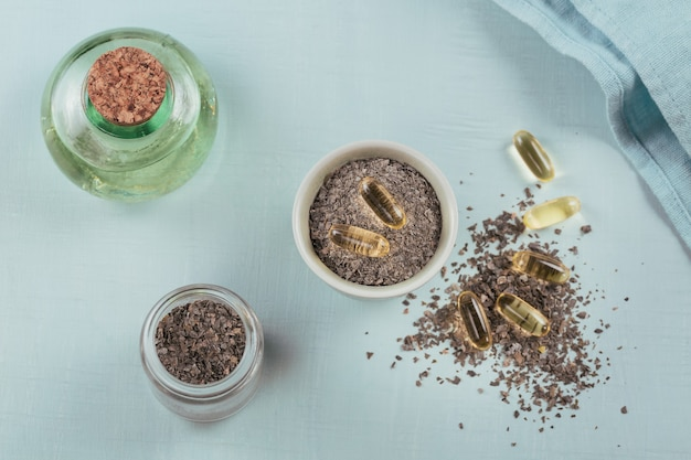 Capsule di gelatina con olio di alghe omega e alghe su fondo azzurro. supplementi dietetici.
