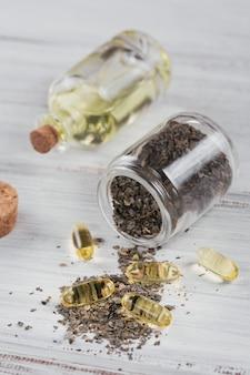 Capsule di gelatina con olio di alghe omega e alghe su fondo di legno bianco. supplementi dietetici.