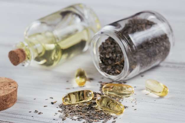 Capsule di gelatina con olio di alghe omega e alghe sul tavolo di legno bianco
