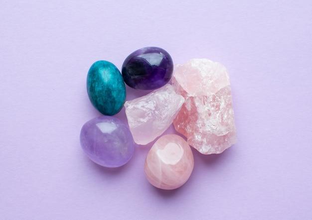 Minerali di pietre preziose su una superficie rosa