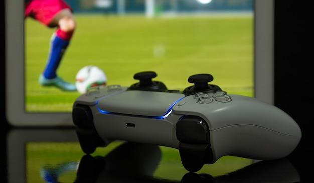 Controller di gioco next gen con partita di calcio sullo schermo