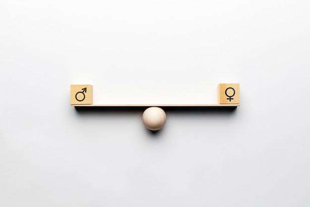 Concetto di uguaglianza di genere su scale astratte con icone maschili e femminili.