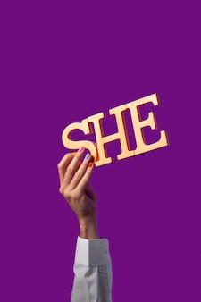 Persona fluida di genere che tiene un pronome isolato su viola