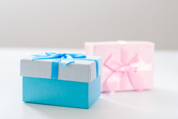 Regali di genere per bambini. scatole regalo blu e rosa su sfondo bianco. celebrazione delle vacanze.