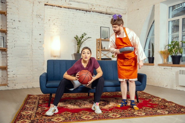 Stereotipi sessuali. moglie e marito fanno cose insolite per il loro genere nei significati sociali, senso. uomo che cucina la cena mentre la donna si allena nel basket con la palla in soggiorno.