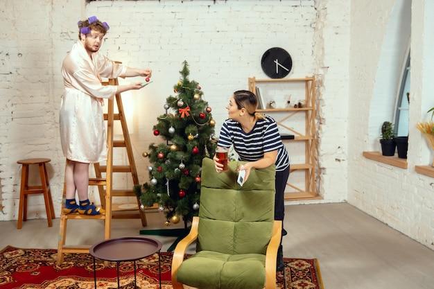Stereotipi sessuali. moglie e marito fanno cose insolite per il loro genere nei significati sociali, senso. uomo che decora l'albero di natale per la festa di capodanno, donna che beve birra annoiata, guardando la tv.