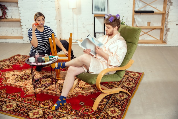 Stereotipi sessuali. moglie e marito fanno cose insolite per il loro genere nei significati sociali, senso. l'uomo ha una giornata di bellezza, fa l'acconciatura, legge riviste mentre la donna ripara tavolo, sedie.