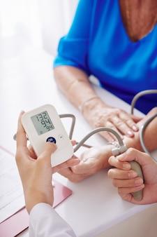 Medico di base che controlla la pressione sanguigna