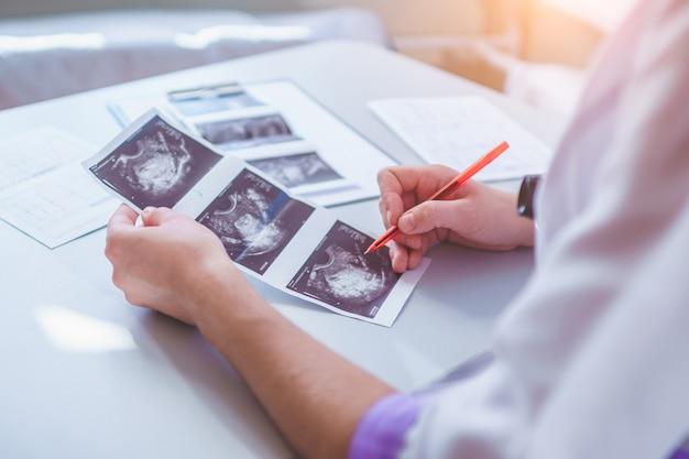 Il medico di famiglia esamina le immagini ecografiche del paziente durante un controllo sanitario e una consultazione. sanità e medicina. diagnosi e trattamento della malattia